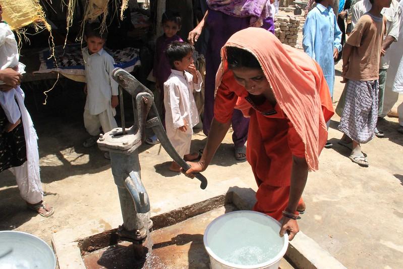 Eine Frau pumpt Wasser aus einem Brunnen. Viele Menschen haben noch immer keinen Zugang zu sauberem Wasser